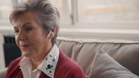 Agente de comercialización mayor que habla con el cliente usando los auriculares almacen de metraje de vídeo