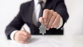 Agente de hipoteca que da llaves del apartamento al comprador de las propiedades inmobiliarias, contrato de la propiedad imagenes de archivo