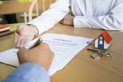 Agente de la propiedad inmobiliaria con el cliente después de la firma de contrato de la casa de compra imagen de archivo