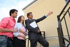 Agente de la propiedad inmobiliaria con los pares jovenes Foto de archivo libre de regalías