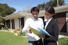 Agente de la propiedad inmobiliaria de pie con el cliente Foto de archivo libre de regalías