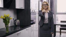 Agente de la propiedad inmobiliaria mayor hermoso que muestra llaves de la casa almacen de metraje de vídeo