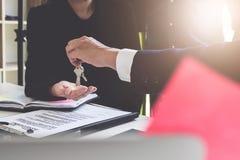 Agente de la propiedad inmobiliaria que da llaves de la casa al acuerdo del cliente y de la muestra adentro fotografía de archivo