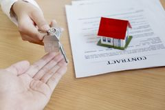 Agente de la propiedad inmobiliaria que da llaves de la casa al acuerdo del dueño y de la muestra en oficina imagen de archivo