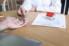 Agente de la propiedad inmobiliaria que da llaves de la casa al acuerdo del dueño y de la muestra en oficina fotos de archivo
