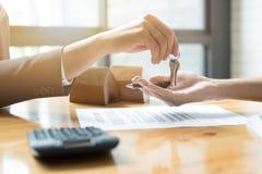 Agente de la propiedad inmobiliaria que da llaves de la casa para servir y para firmar el acuerdo en offi Fotos de archivo libres de regalías