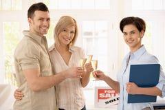 Agente de la propiedad inmobiliaria que felicita pares imagen de archivo