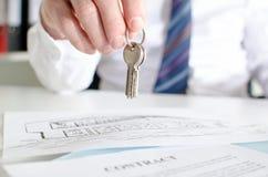 Agente de la propiedad inmobiliaria que lleva a cabo llaves de la casa Imagen de archivo