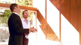 Agente de la propiedad inmobiliaria que muestra a casa al cliente y a la sonrisa almacen de video