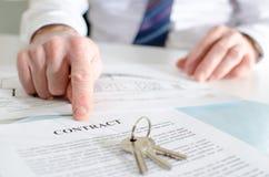 Agente de la propiedad inmobiliaria que muestra un contrato Fotos de archivo libres de regalías
