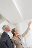 Agente de la propiedad inmobiliaria sonriente que muestra el techo al comprador potencial Foto de archivo