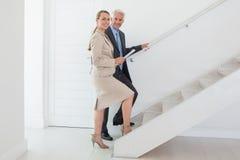 Agente de la propiedad inmobiliaria sonriente que muestra las escaleras al comprador potencial Foto de archivo libre de regalías