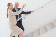 Agente de la propiedad inmobiliaria sonriente que muestra las escaleras al comprador potencial Fotos de archivo