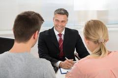 Agente de la propiedad inmobiliaria Talking To Couple en oficina Imagen de archivo