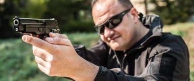 Agente de polícia e escolta que apontam a pistola para proteger do atacante imagens de stock