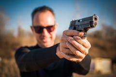 Agente de polícia e escolta que apontam a pistola para proteger do atacante imagens de stock royalty free