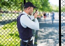 agente de segurança do parque que crava com o Walkietalkie e o ponto a algo fotografia de stock