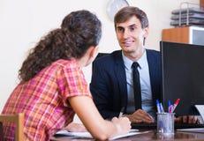 Agente de seguros e cliente que discutem termos do acordo Imagem de Stock Royalty Free