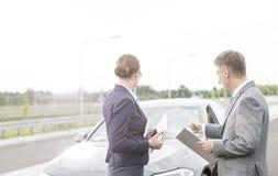 Agente de seguros que discute com a mulher de negócios ao apontar no carro da divisão contra o céu imagens de stock