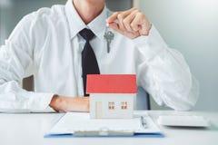 Agente de venta que da la casa dominante al contrato del acuerdo del cliente y de la muestra, concepto del hogar del seguro fotos de archivo libres de regalías