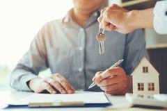 Agente de venta que da la casa dominante al contrato del acuerdo del cliente y de la muestra, concepto del hogar del seguro fotografía de archivo libre de regalías
