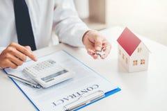 Agente de venta que da la casa dominante al contrato del acuerdo del cliente y de la muestra, concepto del hogar del seguro foto de archivo libre de regalías