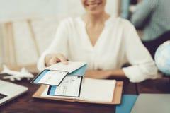 Agente de viagens Holding Tickets na agência de viagens foto de stock