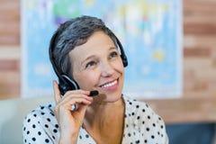 Agente de viajes sonriente que se sienta en su escritorio Imágenes de archivo libres de regalías