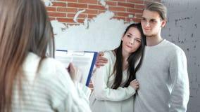 Agente de vivienda femenino que habla con la familia joven de los pares y que escribe el documento para comprar el nuevo apartame almacen de video