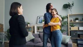 Agente de vivienda que da llaves a los compradores de nuevo besarse del apartamento, del marido y de la esposa metrajes