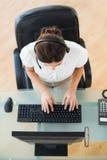 Agente del centro de atención telefónica que mecanografía mientras que en una llamada Imagenes de archivo