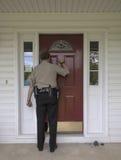 Agente delle forze dell'ordine che batte su una porta Immagini Stock Libere da Diritti