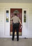 Agente delle forze dell'ordine che batte su una porta Immagini Stock