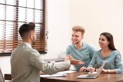 Agente di assicurazione che consulta le giovani coppie immagine stock