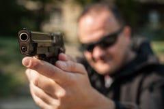 Agente di polizia e guardia del corpo che indicano pistola per proteggere dall'attaccante fotografia stock