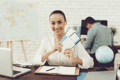Agente di viaggi Holding Tickets nell'agenzia di viaggi Fotografie Stock