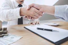 Agente e cliente dell'agente immobiliare che stringono le mani dopo la firma dei capitolati d'oneri per l'acquisto della realt? d fotografie stock libere da diritti