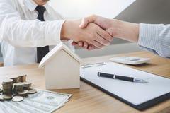 Agente e cliente do corretor imobiliário que agitam as mãos após o signin imagem de stock