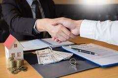 Agente e segno dello sviluppatore di bene immobile sul documento che fornisce le chiavi di nuova casa, agente della proprietà che immagine stock