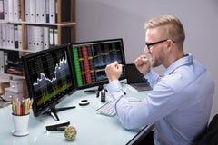 Agente emocionado Looking At Graph del mercado de acción en el ordenador foto de archivo