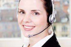Agente femenino joven sonriente del callcenter con las auriculares Foto de archivo libre de regalías