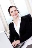 Agente femenino joven sonriente del callcenter con las auriculares Imagen de archivo libre de regalías