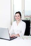 Agente femenino joven sonriente del callcenter con las auriculares Imagen de archivo