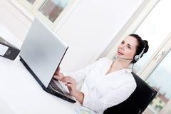 Agente femenino joven sonriente del callcenter con las auriculares Imágenes de archivo libres de regalías
