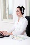 Agente femenino joven sonriente del callcenter con las auriculares Imagenes de archivo