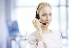 Agente femenino joven sonriente del servicio de atención al cliente con las auriculares Imágenes de archivo libres de regalías