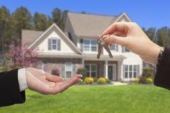 Agente Handing Over as chaves da casa na frente da casa nova Fotografia de Stock Royalty Free