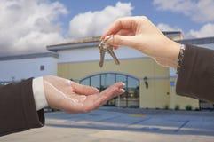 Agente Handing Over as chaves na frente do escritório para negócios Fotografia de Stock Royalty Free