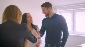 Agente immobiliare caucasico femminile che fornisce le chiavi dalla nuova casa alle giovani coppie emozionanti felici