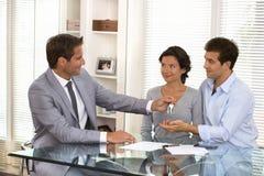 Agente immobiliare che fornisce le chiavi ai nuovi proprietari Fotografia Stock